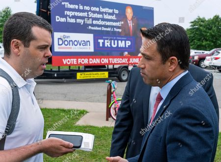 Former Rep. Michael Grimm right, speaks to reporter as he attends a property tax protest rally in the Staten Island borough of New York, Sat. . Grimm is opposing Dan Donovan, R-N.Y., seen on a campaign sign in background, for the Republican Congressional primary for the 11th Congressional District