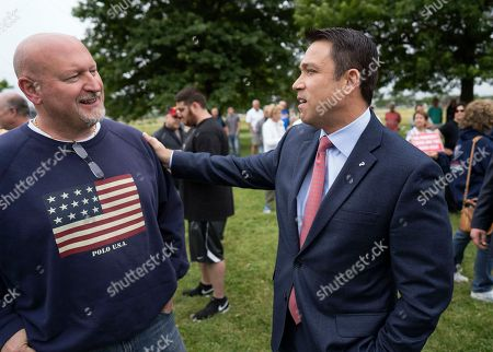 Former Rep. Michael Grimm greets a participant as he attends a property tax protest in the Staten Island borough of New York, . Grimm is opposing incumbent Dan Donovan, R-N.Y., for the Republican Congressional primary for the 11th Congressional District