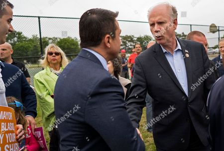 Incumbent Rep. Dan Donovan, R-N.Y., right, shakes hands with former Rep. Michael Grimm, as they attend a property tax protest rally in the Staten Island borough of New York, . Grimm and Donavan are running against one another in the Republican Congressional primary for the 11th Congressional District