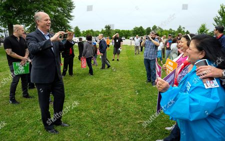 Incumbent Rep. Dan Donovan, R-N.Y., takes a photos of participants as he attends a property tax protest rally in the Staten Island borough of New York, Sat. . Donavan is running against former Rep. Michael Grimm in the Republican Congressional primary for the 11th Congressional District