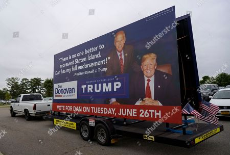A campaign sign on a trailer showing Rep. Dan Donovan, R-N.Y., right, rolls past a tax protest rally in the Staten Island borough of New York, Sat., as Donavan attends. Donavan is running against former Rep. Michael Grimm in the Republican Congressional primary for the 11th Congressional District