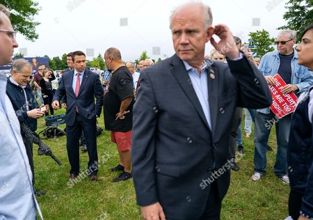 Former Rep. Michael Grimm, background center left, and incumbent Rep. Dan Donovan, R-N.Y., center right, attend a property tax protest rally in the Staten Island borough of New York, . Grimm and Donavan are running against one another in the Republican Congressional primary for the 11th Congressional District