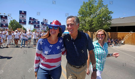 A supporter, left, poses for a photograph with Mitt and Ann Romney during the Strawberry Day Parade, in Pleasant Grove, Utah. Romney is flashing his familiar smile at city parks and backyards in Utah's mountains and suburbs this week, making his final pitch after being forced into a Republican primary against a conservative state lawmaker. At stake is being the party's representative to vie for the Senate seat long held by retiring Republican Sen. Orrin Hatch