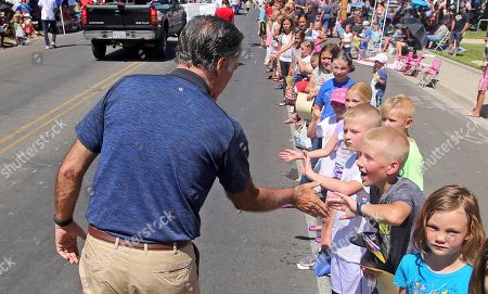 Mitt and Ann Romney greets people during the Strawberry Day Parade, in Pleasant Grove, Utah. Romney is flashing his familiar smile at city parks and backyards in Utah's mountains and suburbs this week, making his final pitch after being forced into a Republican primary against a conservative state lawmaker. At stake is being the party's representative to vie for the Senate seat long held by retiring Republican Sen. Orrin Hatch