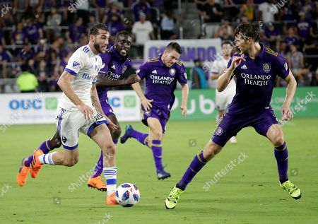 Stock Image of Montreal Impact's Ignacio Piatti, left, moves the ball against the Orlando City defense including Jonathan Spector, right, during the second half of an MLS soccer match, in Orlando, Fla