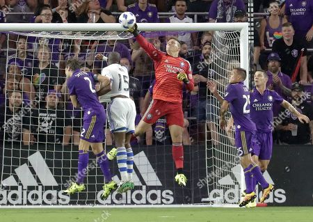 Orlando City goalkeeper Joseph Bendik, center, blocks a shot next to Orlando City's Jonathan Spector, left, and Montreal Impact's Rod Fanni (15) during the first half of an MLS soccer match, in Orlando, Fla
