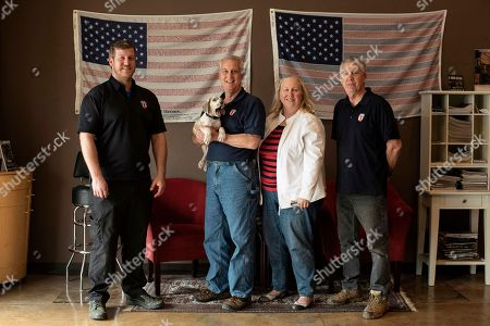 The owners and employees of Honor Defense, a gunmaker in Gainesville, Ga., pose in the company's lobby. Standing, left to right, are Pete Ramey, who works on the assembly line, Gary Ramey, the company's owner, his wife and company business manager, Pam Ramey, and Richard Moore, who works on the assembly line