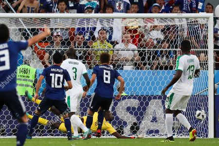 Senegal goalkeeper Khadim Ndiaye fails to stop a kick from Japan's Takashi Inui during the group H match between Japan and Senegal at the 2018 soccer World Cup at the Yekaterinburg Arena in Yekaterinburg, Russia