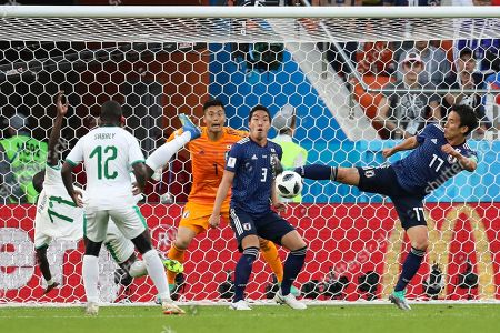 Senegal's Cheikh Ndoye, left, and Japan's Makoto Hasebe, right, challenge for the ball during the group H match between Japan and Senegal at the 2018 soccer World Cup at the Yekaterinburg Arena in Yekaterinburg, Russia