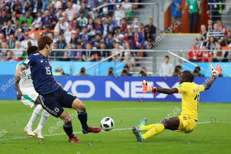 Japan's Yuya Osako, left, tries to score against Senegal goalkeeper Khadim Ndiaye during the group H match between Japan and Senegal at the 2018 soccer World Cup at the Yekaterinburg Arena in Yekaterinburg, Russia