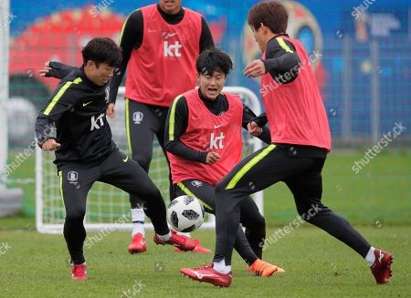 South Korea's Lee Seung-woo, centre, Go Yo-han, left, and their teammate attend South Korea's official training in Lomonosov near St. Petersburg, Russia, at the 2018 soccer World Cup