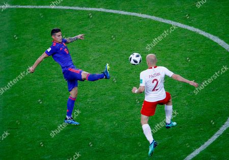 James Rodriguez of Colombia and Michal Pazdan of Poland in action during the FIFA World Cup 2018 group H preliminary round soccer match between Poland and Colombia in Kazan, Russia, 24 June 2018. (RESTRICTIONS APPLY: Editorial Use Only, not used in association with any commercial entity - Images must not be used in any form of alert service or push service of any kind including via mobile alert services, downloads to mobile devices or MMS messaging - Images must appear as still images and must not emulate match action video footage - No alteration is made to, and no text or image is superimposed over, any published image which: (a) intentionally obscures or removes a sponsor identification image; or (b) adds or overlays the commercial identification of any third party which is not officially associated with the FIFA World Cup)