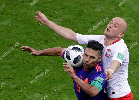 Colombia's Radamel Falcao, left, and Poland's Michal Pazdan battle for the ball during the group H match between Poland and Colombia at the 2018 soccer World Cup at the Kazan Arena in Kazan, Russia