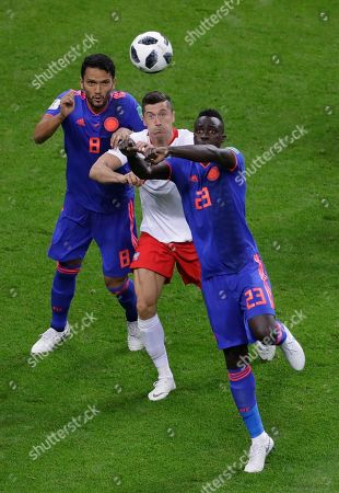 Poland's Robert Lewandowski, center, battles with Colombia's Abel Aguilar, left, and Colombia's Davinson Sanchez during the group H match between Poland and Colombia at the 2018 soccer World Cup at the Kazan Arena in Kazan, Russia