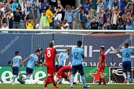 Toronto FC goalkeeper Alex Bono lies on the grass as New York City FC forward Jo Inge Berget (9) scores a goal during the second half of an MLS soccer game, in New York