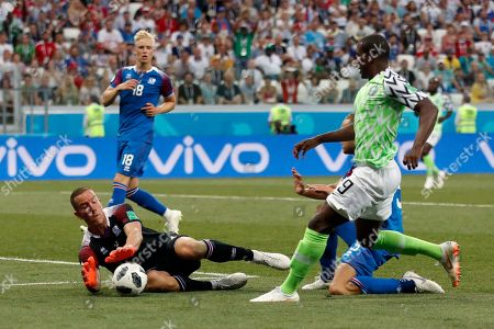 Iceland goalkeeper Hannes Halldorsson, left, makes a save in front of Nigeria's Odion Ighalo, right, during the group D match between Nigeria and Iceland at the 2018 soccer World Cup in the Volgograd Arena in Volgograd, Russia