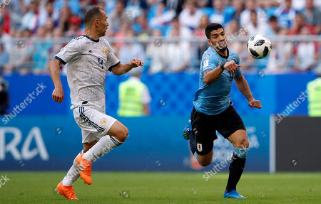 Russia's Yuri Gazinsky, left, and Uruguay's Luis Suarez challenge for the ball during the group A match between Uruguay and Russia at the 2018 soccer World Cup at the Samara Arena in Samara, Russia