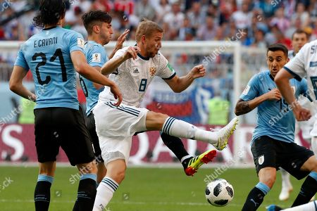 Russia's Yuri Gazinsky, center, fights for the ball with Uruguay's Rodrigo Bentancur during the group A match between Uruguay and Russia at the 2018 soccer World Cup at the Samara Arena in Samara, Russia