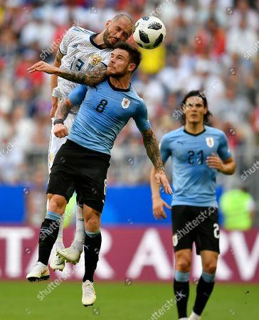 Russia's Fyodor Kudryashov, left, and Uruguay's Nahitan Nandez compete for the ball during the group A match between Uruguay and Russia at the 2018 soccer World Cup at the Samara Arena in Samara, Russia