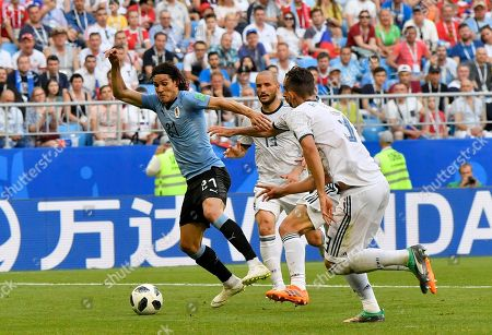 Uruguay's Edinson Cavani, left, take the ball away from Russia's Ilya Kutepov, right, and Fyodor Kudryashov during the group A match between Uruguay and Russia at the 2018 soccer World Cup at the Samara Arena in Samara, Russia