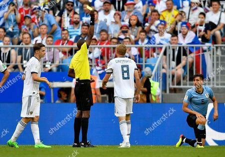 Referee Malang Diedhiou of Senegal shows yellow card to Russia's Yuri Gazinsky, second right, during the group A match between Uruguay and Russia at the 2018 soccer World Cup at the Samara Arena in Samara, Russia