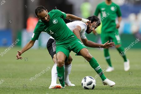 Saudi Arabia's Abdullah Otayf, left, and Egypt's Marwan Mohsen challenge for the ball during the group A match between Saudi Arabia and Egypt at the 2018 soccer World Cup at the Volgograd Arena in Volgograd, Russia
