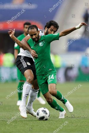 Saudi Arabia's Abdullah Otayf, front, and Egypt's Marwan Mohsen challenge for the ball during the group A match between Saudi Arabia and Egypt at the 2018 soccer World Cup at the Volgograd Arena in Volgograd, Russia