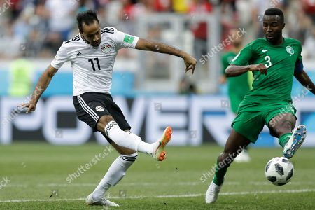 Egypt's Kahraba, left, kicks past Saudi Arabia's Osama Hawsawi during the group A match between Saudi Arabia and Egypt at the 2018 soccer World Cup at the Volgograd Arena in Volgograd, Russia