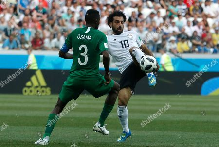 Saudi Arabia's Osama Hawsawi, left, and Egypt's Mohamed Salah challenge for the ball during the group A match between Saudi Arabia and Egypt at the 2018 soccer World Cup at the Volgograd Arena in Volgograd, Russia