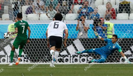 Saudi Arabia's Salman Alfaraj, left, scores his side's opening goal from the penalty spot past Egypt goalkeeper Essam El Hadary during the group A match between Saudi Arabia and Egypt at the 2018 soccer World Cup at the Volgograd Arena in Volgograd, Russia