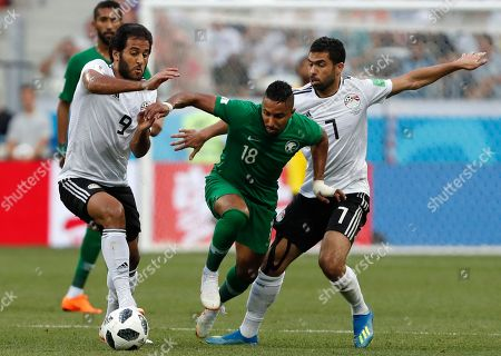 Saudi Arabia's Salem Aldawsari is challenged by Egypt's Marwan Mohsen, left, and Ahmed Fathi, right, during the group A match between Saudi Arabia and Egypt at the 2018 soccer World Cup at the Volgograd Arena in Volgograd, Russia