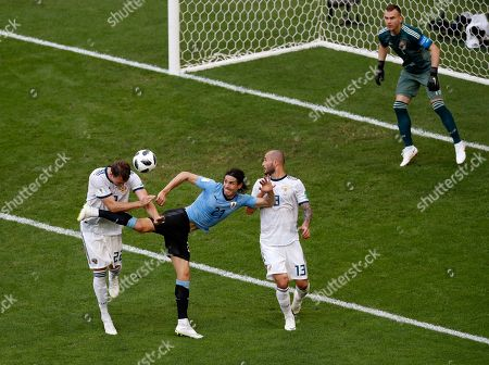Russia's Artyom Dzyuba, left, and Russia's Fyodor Kudryashov, second right, fight for the ball with Uruguay's Edinson Cavani, center, as Russia goalkeeper Igor Akinfeev looks at them during the group A match between Uruguay and Russia at the 2018 soccer World Cup at the Samara Arena in Samara, Russia