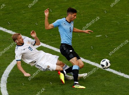 Russia's Yuri Gazinsky, left, vies for the ball with Uruguay's Rodrigo Bentancur during the group A match between Uruguay and Russia at the 2018 soccer World Cup at the Samara Arena in Samara, Russia
