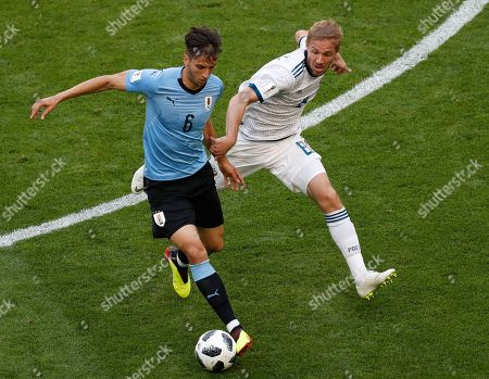 Uruguay's Rodrigo Bentancur, left, and Russia's Yuri Gazinsky challenge for the ball during the group A match between Uruguay and Russia at the 2018 soccer World Cup at the Samara Arena in Samara, Russia