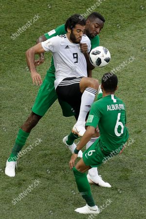 Egypt's Marwan Mohsen plays the ball challenged by Saudi Arabia's Mohammed Alburayk (6) and Osama Hawsawi during the group A match between Saudi Arabia and Egypt at the 2018 soccer World Cup at the Volgograd Arena in Volgograd, Russia