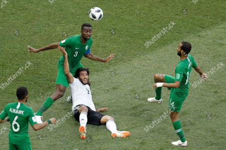 Egypt's Marwan Mohsen falls challenged by Saudi Arabia's Mohammed Alburayk, right, and Osama Hawsawi, bak left, during the group A match between Saudi Arabia and Egypt at the 2018 soccer World Cup at the Volgograd Arena in Volgograd, Russia