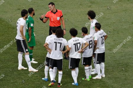Surrounded by Egyptian players Saudi Arabia's Abdullah Otayf talks to referee Wilmar Roldan from Colombia during the group A match between Saudi Arabia and Egypt at the 2018 soccer World Cup at the Volgograd Arena in Volgograd, Russia
