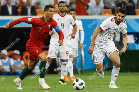 Cristiano Ronaldo of Portugal (L) in action against Saeid Ezatolahi of Iran during the FIFA World Cup 2018 group B preliminary round soccer match between Iran and Portugal at Mordovia Arena Saransk, in Saransk, Russia, 25 June 2018. (RESTRICTIONS APPLY: Editorial Use Only, not used in association with any commercial entity - Images must not be used in any form of alert service or push service of any kind including via mobile alert services, downloads to mobile devices or MMS messaging - Images must appear as still images and must not emulate match action video footage - No alteration is made to, and no text or image is superimposed over, any published image which: (a) intentionally obscures or removes a sponsor identification image; or (b) adds or overlays the commercial identification of any third party which is not officially associated with the FIFA World Cup)