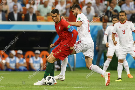Cristiano Ronaldo of Portugal (L) in action against Saeid Ezatolahi of Iran (C) during the FIFA World Cup 2018 group B preliminary round soccer match between Iran and Portugal at Mordovia Arena Saransk, in Saransk, Russia, 25 June 2018. (RESTRICTIONS APPLY: Editorial Use Only, not used in association with any commercial entity - Images must not be used in any form of alert service or push service of any kind including via mobile alert services, downloads to mobile devices or MMS messaging - Images must appear as still images and must not emulate match action video footage - No alteration is made to, and no text or image is superimposed over, any published image which: (a) intentionally obscures or removes a sponsor identification image; or (b) adds or overlays the commercial identification of any third party which is not officially associated with the FIFA World Cup)