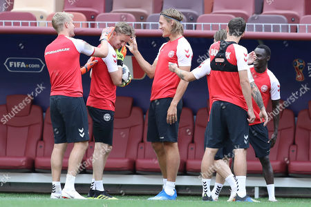 Denmark goalkeeper Jonas Lossl, left, and Jannik Vestergaard, center, joke with Frederik Ronnow during Denmark's official training at the eve of the group C match between France and Denmark at the 2018 soccer World Cup in the Luzhniki Stadium in Moscow, Russia