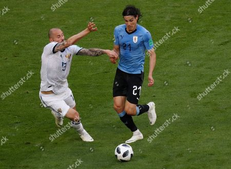 Uruguay's Edinson Cavani, right, fights for the ball with Russia's Fyodor Kudryashov during the group A match between Uruguay and Russia at the 2018 soccer World Cup at the Samara Arena in Samara, Russia
