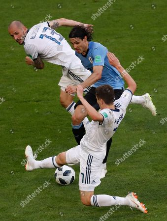 Uruguay's Edinson Cavani, center, challenges for the ball with Russia's Fyodor Kudryashov, left, and Daler Kuziaev during the group A match between Uruguay and Russia at the 2018 soccer World Cup at the Samara Arena in Samara, Russia