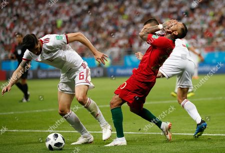 Portugal's Ricardo Quaresma, right, flls after a clash with Iran's Saeid Ezatolahi, left, during the group B match between Iran and Portugal at the 2018 soccer World Cup at the Mordovia Arena in Saransk, Russia