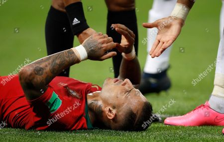 Portugal's Ricardo Quaresma lies on the ground after a clash with Iran's Saeid Ezatolahi as hand are offered to help him up during the group B match between Iran and Portugal at the 2018 soccer World Cup at the Mordovia Arena in Saransk, Russia