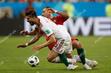 Iran's Saeid Ezatolahi front, falls as he is tackled by Portugal's Ricardo Quaresma during the group B match between Iran and Portugal at the 2018 soccer World Cup at the Mordovia Arena in Saransk, Russia