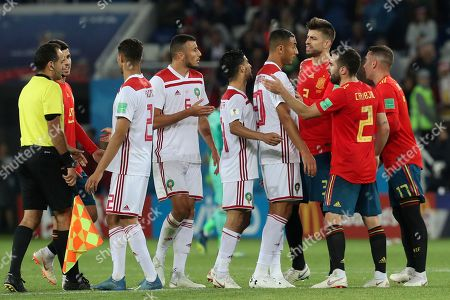 Spain's Gerard Pique, third right, argues with Morocco's Aziz Bouhaddouz, fourth right, during the group B match between Spain and Morocco at the 2018 soccer World Cup at the Kaliningrad Stadium in Kaliningrad, Russia