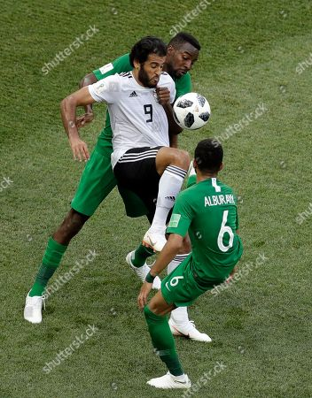 Egypt's Marwan Mohsen, middle, is challenged by Saudi Arabia's Osama Hawsawi, back and teammate Mohammed Alburayk during the group A match between Saudi Arabia and Egypt at the 2018 soccer World Cup at the Volgograd Arena in Volgograd, Russia