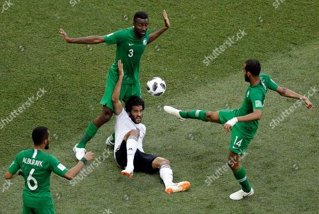 Egypt's Marwan Mohsen, bottom, is challenged by Saudi Arabia's Osama Hawsawi, back, and teammate Abdullah Otayf, right, during the group A match between Saudi Arabia and Egypt at the 2018 soccer World Cup at the Volgograd Arena in Volgograd, Russia