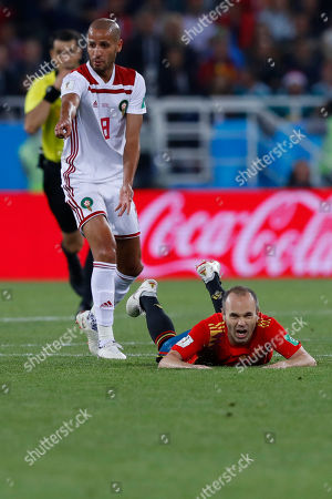 Morocco's Karim El Ahmadi, left, gestures while Spain's Andres Iniesta lies on the ground during the group B match between Spain and Morocco at the 2018 soccer World Cup at the Kaliningrad Stadium in Kaliningrad, Russia