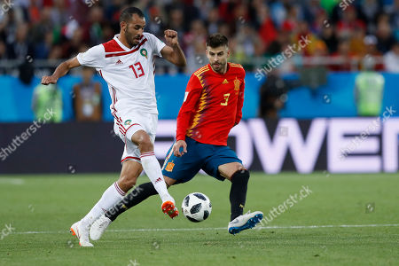Morocco's Khalid Boutaib, left, and Spain's Gerard Pique challenge for the ball during the group B match between Spain and Morocco at the 2018 soccer World Cup at the Kaliningrad Stadium in Kaliningrad, Russia